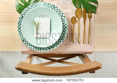 Green color table setting with card and floral decor on wooden surface