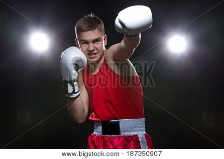 Teenage boxer in red form and white gloves, backlights. Studio shot on black background. Copy space.