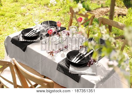 Table setting with glass stands and flowers in vases