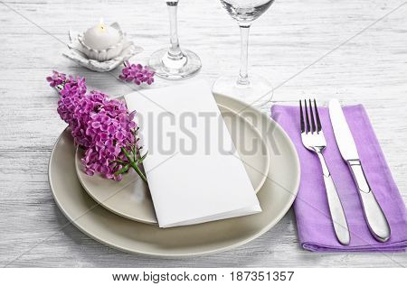 Beautiful festive table setting with lilac flower decor on wooden background