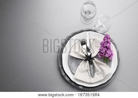 Beautiful festive table setting with lilac flower decor on grey background