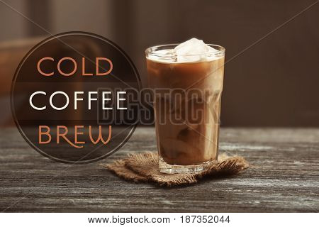 Glass of cold brewed coffee with milk on wooden table