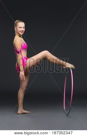 beautiful blond teen age gymnast girl making exercises with hula hoop. Studio shot on black background. Copy space.