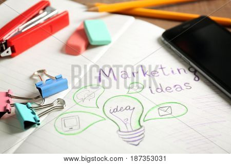 Text MARKETING IDEAS and drawing of light bulb in notebook