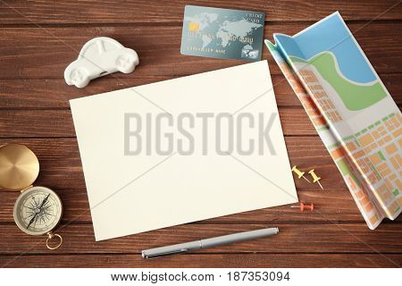 Blank notepad page, credit card and travel accessories on wooden background