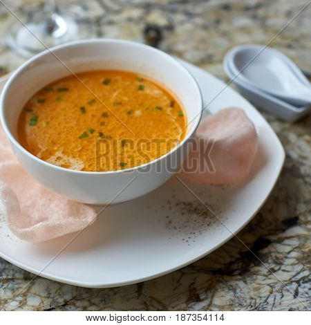 Creamy crab soup served with crab chips and glass of white wine on marble backround