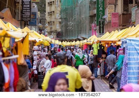 Asian Street Market Kuala Lumpur 09/09/2016. Blurred view of a busy daytime street market. Street busy with people and lined with yellow roofed stalls.