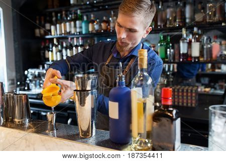 alcohol drinks, people and luxury concept - barman with shaker and bottles squeezing juice into jigger and preparing cocktail at bar