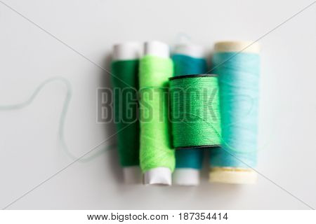 needlework, craft, sewing and tailoring concept - green and blue thread spools on table