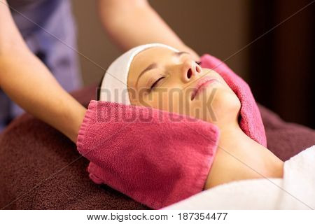 people, beauty, lifestyle and relaxation concept - beautiful young woman lying with closed eyes and having face massage with terry gloves at spa