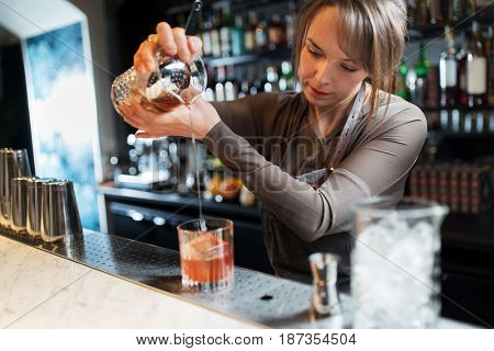 alcohol drinks, people and luxury concept - barmaid with glass and jug preparing cocktail at bar