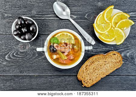 Soup saltwort with lemon, meat, pickles, tomato sauce olives in a bowl, bread and a spoon on the background of a wooden board from above