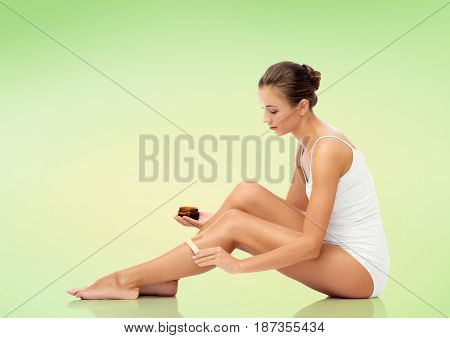 beauty, hair removal and people concept - beautiful woman with applicator applying depilatory wax to her leg over green background