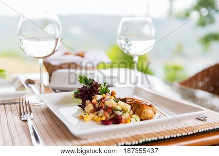 food, dinner and eating concept - vegetable salad with meat on plate and glasses of water at restaurant