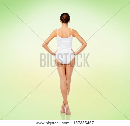 beauty, people and bodycare concept - beautiful young woman in white underwear from back over green background