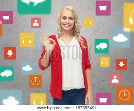 gesture, multimedia and people concept - happy smiling young woman in red cardigan showing ok hand sign over gray background with menu icons