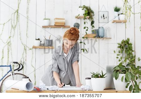 Occupation and profession. Skilled attractive redhead European woman architect busy making notes while filling in technical documentation working on architectural plan standing over blueprints