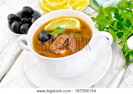 Soup saltwort with lemon, meat, pickles, tomato sauce and olives in a white bowl, parsley on a wooden board background