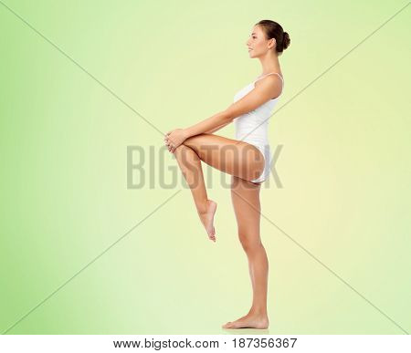 beauty, people and bodycare concept - beautiful young woman in white underwear over green background