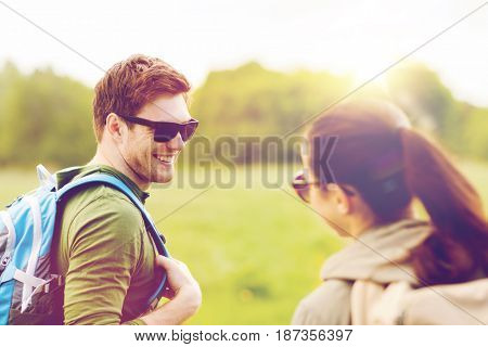 travel, hiking, backpacking, tourism and people concept - smiling couple with backpacks in nature looking at each other