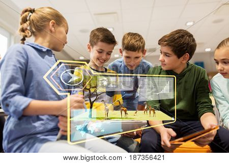 education, technology and people concept - group of happy kids with tablet pc computers learning at school over wild animals on virtual screen