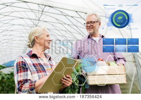 organic farming, agriculture and people concept - senior couple with box of vegetables and clipboard at farm greenhouse