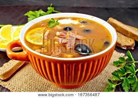 Soup saltwort with lemon, meat, pickles, tomato sauce olives in a bowl on a sacking, bread and parsley on a wooden board background