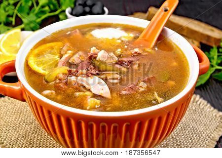 Soup saltwort with lemon, meat, pickles, tomato sauce olives, spoon in a bowl on a sacking on a background of a dark wooden board
