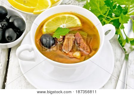 Soup saltwort with lemon, meat, pickles, tomato sauce and olives in a white bowl on a wooden board background