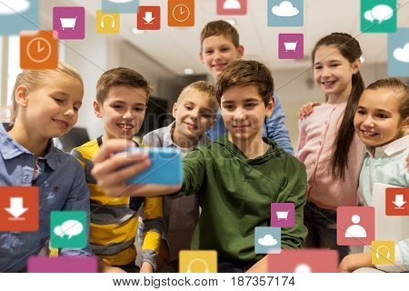technology, children and people concept - group of kids taking selfie with smartphone in corridor and virtual icons