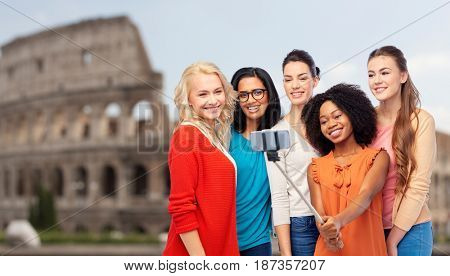 travel, tourism and people concept - international group of happy smiling different women taking picture with smartphone on selfie stick over coliseum background