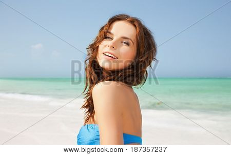 people, summer holidays, vacation and travel concept - happy young woman posing in bikini swimsuit with raised hands over exotic tropical beach and sea shore background