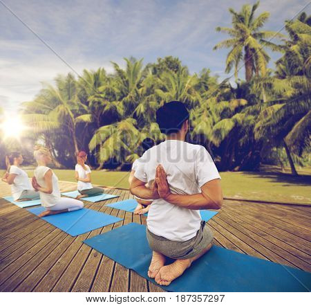 fitness, sport, yoga and healthy lifestyle concept - group of people exercising in reverse prayer pose over natural background with palm trees