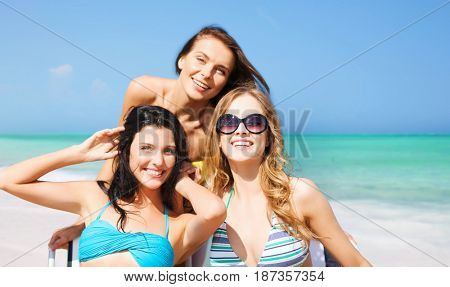 summer holidays, people, leisure, vacation and travel concept - happy women sunbathing on chairs over exotic tropical beach background