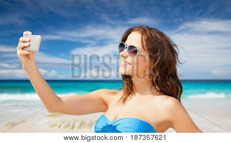 technology, summer holidays, travel and people concept - happy young woman in bikini swimsuit and sunglasses taking selfie with smatphone over beach background