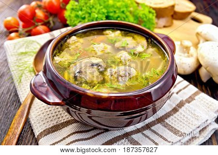 Soup with meatballs, noodles and champignon in a clay bowl on a napkin, parsley, tomatoes, mushrooms and bread on a wooden boards background