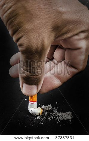 Upside down man hand holding a cigarette with smoke on black background.