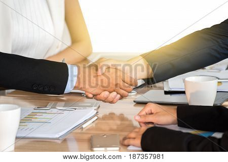 Businessmen shaking hands during a meeting .