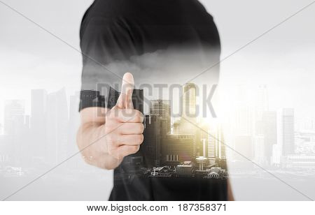gesture and people concept - close up of man hand showing thumbs up over city with double exposure