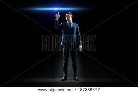 business, technology and people concept - businessman in suit pointing finger to laser light ray over black background