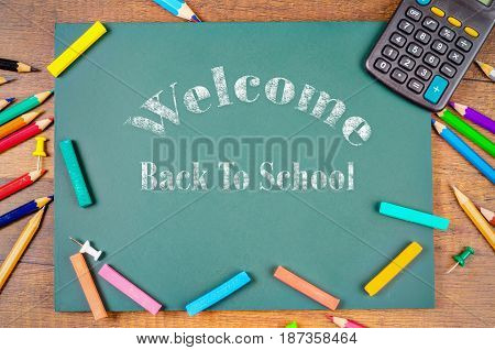 Back to school word with School supplies on green board background.