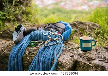 Close up Used equipment for climbing where the rope carabiners and climbing slippers next to the mug on which an empty plate
