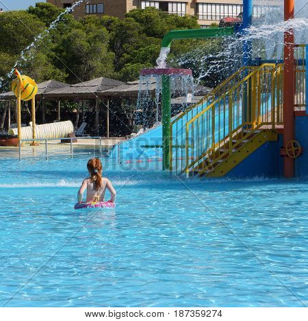 red hair girl behind view in outdoor aquapark
