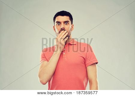 emotion, advertisement and people concept - scared man in polo t-shirt over gray background