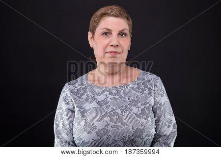 Portrait of friendly senior blond woman on black background