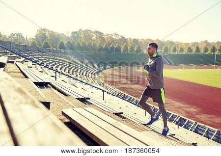 fitness, sport, exercising and people concept - happy young man running upstairs on stadium