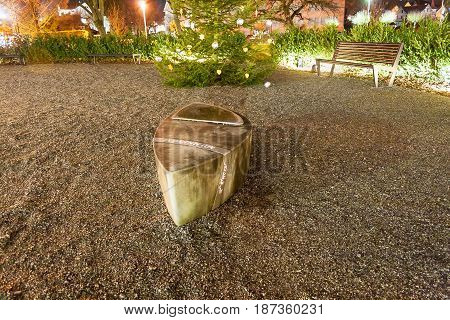photo of Christmas tree, sculpture and bench at the night