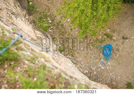 A twisted blue rope climbing rope lying on the ground at the foot of the cliff