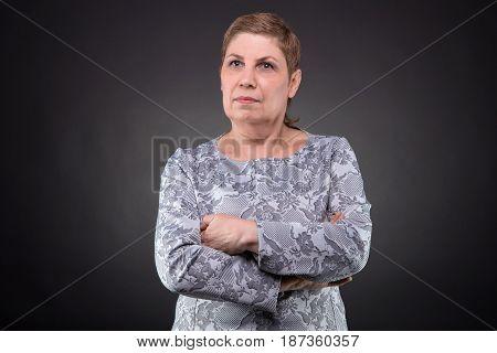 Portrait of dreaming senior woman on dark background