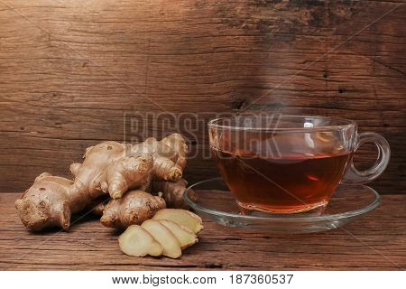Hot ginger water and ginger on wooden table